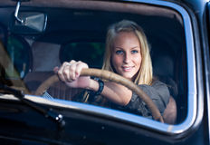 Beautiful blond girl in a black vintage car. Beautiful young blond girl smiling in a black vintage car, holding the streering wheel, shot through the windscreen royalty free stock photography