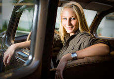 Beautiful blond girl in a black vintage car. Royalty Free Stock Photo