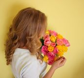 Beautiful blond girl in the blue dress holding bouquet of yellow and pink roses on a light-yellow background. stock images