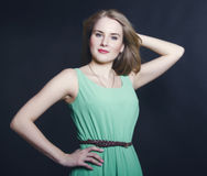 Beautiful blond girl with blue eyes in the green dress smiling o. N a dark background Stock Image