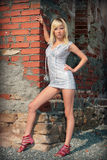 Beautiful blond girl on brick wall Royalty Free Stock Photos