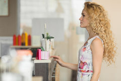 Beautiful blond girl in cafe, choosing some sweets to buy. Stock Image