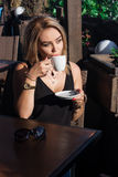 Beautiful blond girl in a cafe on the street stock photo