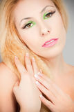 Beautiful blond girl with cat eyes make-up green. Beautiful blond girl with cat eyes make-up in green Royalty Free Stock Images