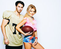 Beautiful blond girl cheerleader with a ball and a quarterback player american football posing with a ball. Super bowl. NFL. Footy Stock Photos