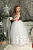 Beautiful blond girl child in a smart white dress in Christmas decorations Royalty Free Stock Photos