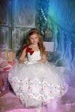 Beautiful blond girl child in a smart white dress in Christmas decorations Royalty Free Stock Photography
