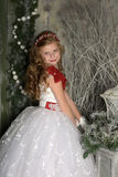 Beautiful blond girl child in a smart white dress in Christmas decorations Stock Photos