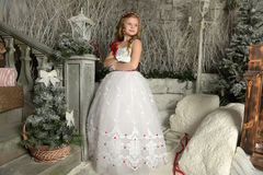 Beautiful blond girl child in a smart white dress in Christmas decorations Stock Photography