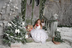 Beautiful blond girl child in a smart white dress is sitting on the porch of the Christmas Royalty Free Stock Images