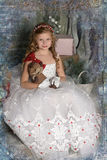 Beautiful blond girl child in a smart white dress with a toy Stock Photography