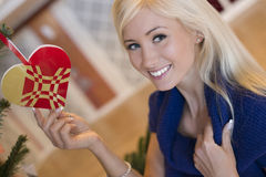 Beautiful blond girl with christmas ornament. Beautiful blond girl next to christmastree ornament smiling blue sweater stock photos