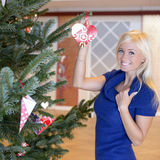 Beautiful blond girl with christmas ornament. Beautiful blond girl next to christmastree ornament smiling blue sweater royalty free stock photography