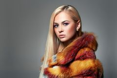 Beautiful Blond Girl in colorful Fur. Winter Style Woman in Luxury Fur. Rainbow, Make-up stock photography