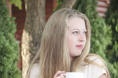 Beautiful blond girl cup of coffee portrait on nature. Beautiful blond girl with cup of coffee portrait on nature stock photos