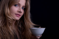 Beautiful blond girl with a cup of tea looking to the camera. Dark tones, low key Royalty Free Stock Image