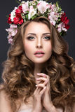 Beautiful blond girl with curls and wreath of purple flowers on her head. Beauty face. Stock Photography