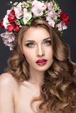 Beautiful blond girl with curls and wreath of purple flowers on her head. Beauty face. Royalty Free Stock Image