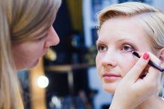 Beautiful girl doing make up, make up artist work stock photo