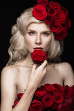 Beautiful blond girl in dress and hat with roses, classic makeup, curls, red lips. Beauty face. Royalty Free Stock Image