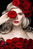 Beautiful blond girl in dress and hat with roses, classic makeup, curls, red lips. Beauty face. Stock Images
