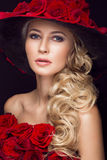 Beautiful blond girl in dress and hat with roses, classic makeup, curls, red lips. Beauty face. Royalty Free Stock Images