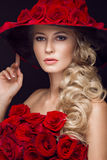 Beautiful blond girl in dress and hat with roses, classic makeup, curls, red lips. Beauty face. Stock Photos