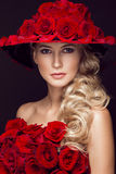 Beautiful blond girl in dress and hat with roses, classic makeup, curls, red lips. Beauty face. Stock Image