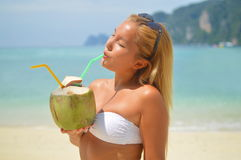 Beautiful blond girl drinkng coconut Stock Photography