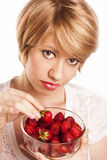 Beautiful blond girl eating strawberries isolated on Royalty Free Stock Images