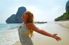 Beautiful blond girl enjoying sun on the beach. Beautiful blond young girl standing and spreading arms near the ocean on the white sand beach Royalty Free Stock Image