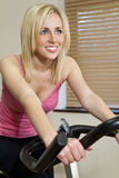 Beautiful Blond Girl On Exercise Bike At The Gym Stock Photo