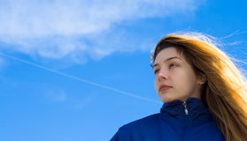 Beautiful blond girl facing the future. With sky as background Stock Photo