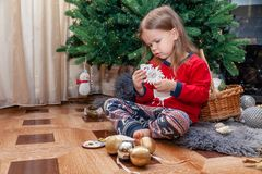 Beautiful blond girl in festive clothes sorts Christmas tree toy stock images