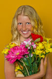 Beautiful blond girl with freckles holding a bouquet of flowers Royalty Free Stock Photos