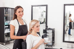 Beautiful blond girl is getting hairstyle by Royalty Free Stock Photos