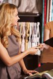 Beautiful blond girl giving credit card. Royalty Free Stock Photo