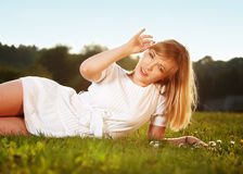 Beautiful blond girl on a grass Royalty Free Stock Images