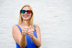 Beautiful blond girl happy pointing fingers thumbs up watching movie with 3D glasses, exciting screaming. portrait Royalty Free Stock Images