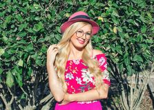Beautiful blond girl with hat and glasses. On open air. Behind her green foliage. Illuminated by the sun. stock photography