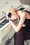 Beautiful blond girl in headband lying on keyboard of white piano with her eyes closed. Back to 1920s.  royalty free stock image