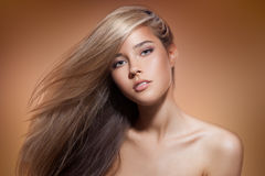 Beautiful Blond Girl. Healthy Long Hair. Brown Background Stock Image