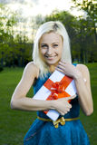 Beautiful blond girl holding box with a gift Royalty Free Stock Photography