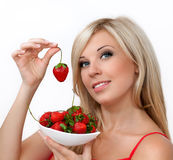Beautiful blond girl holding a strawberry Royalty Free Stock Photo