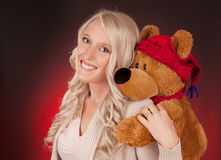 Beautiful blond girl holding a teddy bear Stock Photography