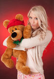 Beautiful blond girl holding a teddy bear Royalty Free Stock Photos