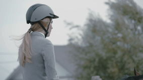 Beautiful blond girl horsewoman wearing a helmet on a horse stock video footage