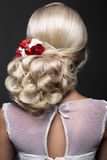 Beautiful blond girl in image of the bride with purple flowers on her head. Beauty face. Hairstyle back view. Portrait of a beautiful blond girl in image of the royalty free stock images