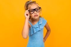 Beautiful Blond Girl In Glasses Close-up On An Orange Studio Background Stock Image