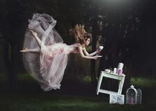 A beautiful blond girl is leaning with a mug of tea over a table. Lack of gravity. Like Alice in Wonderland. A girl with